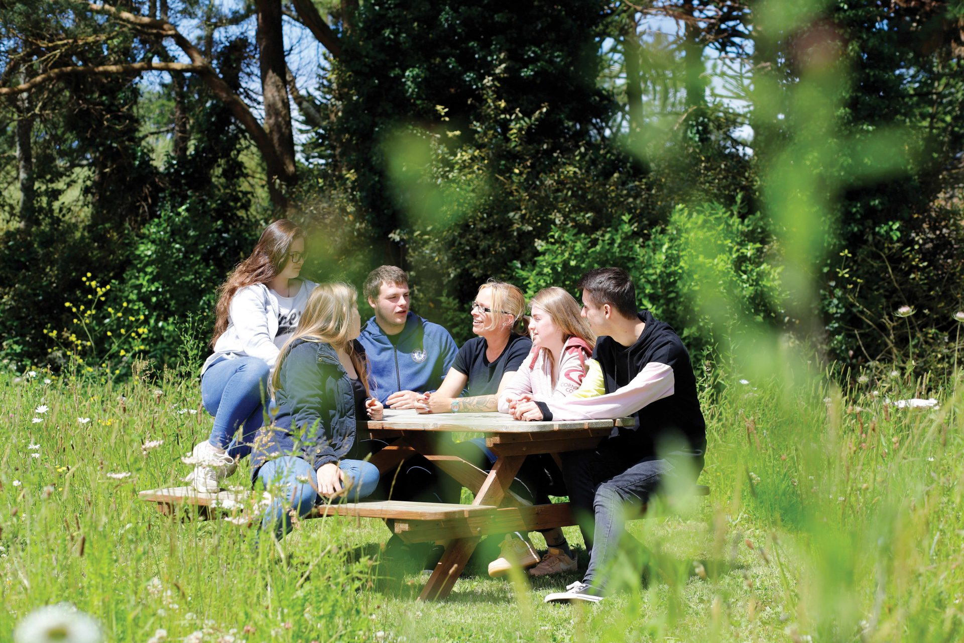 Duchy College students sitting talking in the sunshine outside at the Rosewarne campus